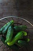 Gherkins in a wire basket on a wooden table top