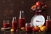 Sieved tomatoes in jars and bottles with fresh tomatoes on a pair of kitchen scales