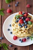 A stack of waffles with raspberries and blueberries