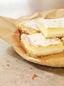 Vier Stücke Kokos-Quark-Kuchen auf Backpapier