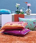 Dekorative bunte Kissen mit Blumenmuster auf orangefarbenem Wollteppich vor Sideboard mit Retro-Vasen und Blüten