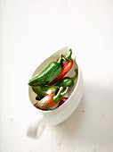 Fresh red and green chilli peppers in a gravy boat