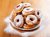 A pile of doughnuts dusted with icing sugar on a plate