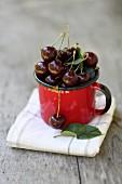 Fresh cherries in an enamel mug