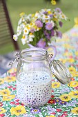 Blueberries in buttermilk in a preserving jar on a garden table