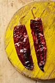 Two dried Guajillo chilli peppers (seen from above)
