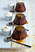 Three toffee puddings served with whipped cream