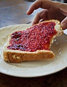 A woman's hands picking up a slice of toast with strawberry jam