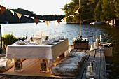 Festlich gedeckter Hochzeitstisch auf Holzterrasse am Wasser