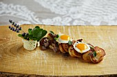 Tiroler (typical Tirolean dish using leftovers) with quail's eggs and fresh marjoram