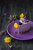 A slice of blueberry cheesecake with dandelion flowers