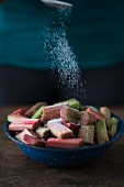 Pieces of rhubarb being sprinkled with sugar
