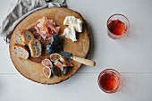 Parma ham, figs, bread and cream cheese on a wooden platter