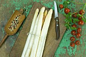 A bundle of fresh white asparagus, tomatoes and parsley on a wooden table, peppercorns in a mortar and a knife