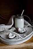 Vegane Kokosmilch in Schraubglas mit Strohhalm auf Tablett