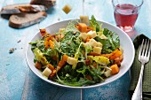 Diced cheese falling into a mixed leaf salad