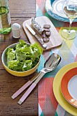 A table laid with colourful accessories, salami, salad and white wine