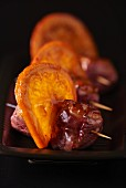 Meet skewers with bacon and candied orange slices