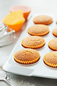 Freshly baked cupcakes in orange paper cases
