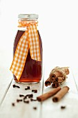 A bottled of spiced syrup with cinnamon and cloves