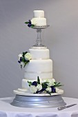 A white, multi-tiered wedding cake decorated with roses