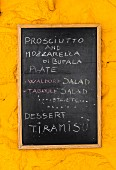Tafel mit Speisenangeboten an einer gelben Wand