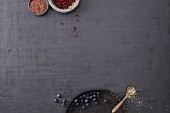 Blueberries and pomegranate seeds on a black surface