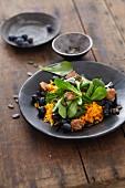 Vegan salad with lamb's lettuce, pumpkin, blueberries, pumpkin seeds and croutons