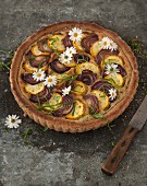 Yellow courgette tart with red onions and edible flowers