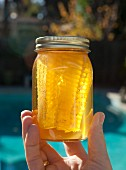 A hand holding a jar of homemade honey with a honeycomb
