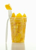 Pieces in pineapple in a plastic cup with a fork
