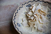 Handmade pasta with flour in a basket bowl