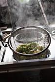 Dampfende grüne und weisse Tagliatelle in einem Sieb