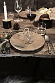 Christmas in a wine cellar: a place setting at a rustic wooden table with wine and candles