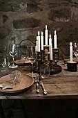Weihnachten im Weinkeller: Gedeck auf rustikalem Holztisch mit Wein und Kerzen