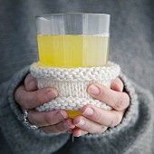 Hands holding a glass of alcohol-free elderflower punch
