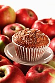 An apple muffin with red apples