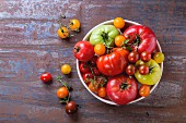 Various types of tomatoes in a bowl on a metal surface (seen from above)