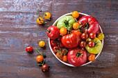 Verschiedene Tomatensorten in einer Schüssel auf Metalluntergrund (Draufsicht)