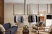 Sofa und Sesseln im Fiftiesstil, im Hintergrund Herrenbekleidung auf abgehängten Kleiderstangen