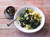 Vegan mashed potatoes with spinach, fresh herbs and pumpkin seeds