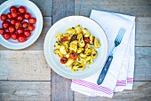 Pasta with fried cherry tomatoes and basil
