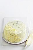 Eine Schwarz-weiss-Torte mit weissen Buttercremerosen garnieren