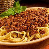 Tagliatelle with a minced meat sauce garnished with basil