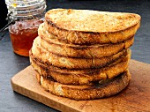 A stack of toast on a chopping board with jam