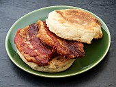 An English muffin with fried pork belly