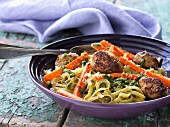 Veal meatballs in a green pesto sauce with noodles