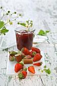 Ein Glas Erdbeer-Rhabarber-Marmelade, frische Erdbeeren und Rhabarber auf Schneidebrett