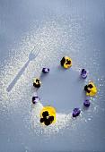 Abdrücke in Puderzucker von Gabel und rundem Gebäck mit Stiefmütterchen
