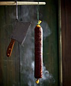 A raw sausage hanging in a smoking chamber